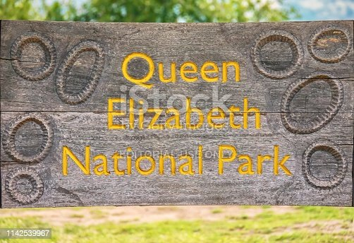 Queen Elizabeth National Park, Uganda - September. 15, 2015. A weathered and cracked wooden sign in the wildlife park, engraved with golden yellow letters and craters, representing the volcanic crater lakes in the park.