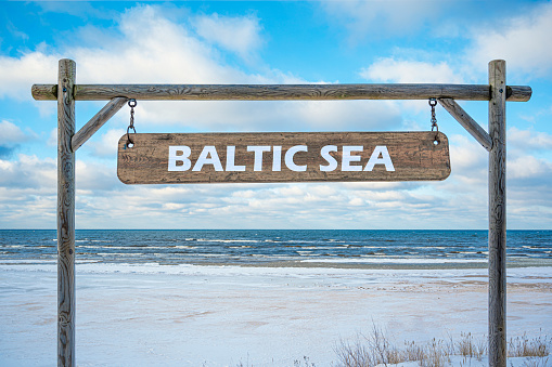 Wooden sign of Baltic sea against blue sky, sea and beach with white sand.