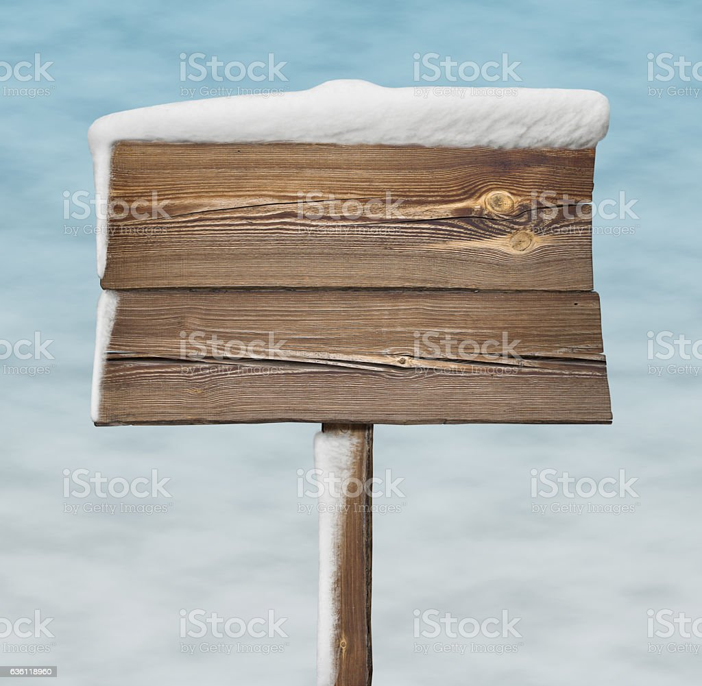 Wooden sign with less snow on it and snow bg stock photo