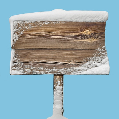 Wooden signpost with snow on it isolated on blue