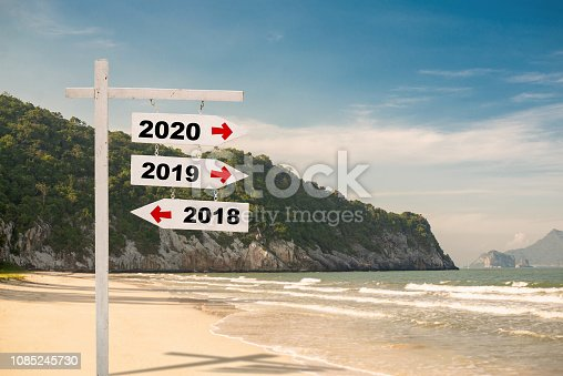 istock wooden sign with text 2020,2019 and 2018 Over Blurred blue sea and sand beach with cloudy blue sky , Image for New year 2019-2020 Concept,Copy space. 1085245730