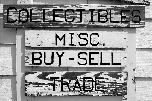 Distressed sales sign outside of antique shop, attached to a white door. Word text listed on the sign includes: collectibles, mics., buy-sell, and trade.
