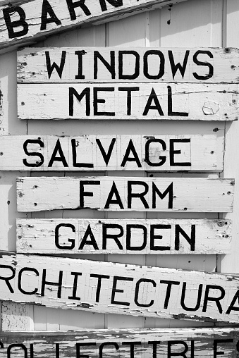 Distressed sales sign outside of antique shop attached to a white door. Words listed on the sign include: windows, metal, salvage, farm, garden, and architecture.