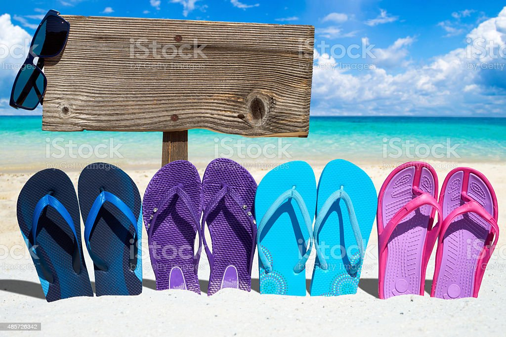Wooden signboard and flip flops stock photo