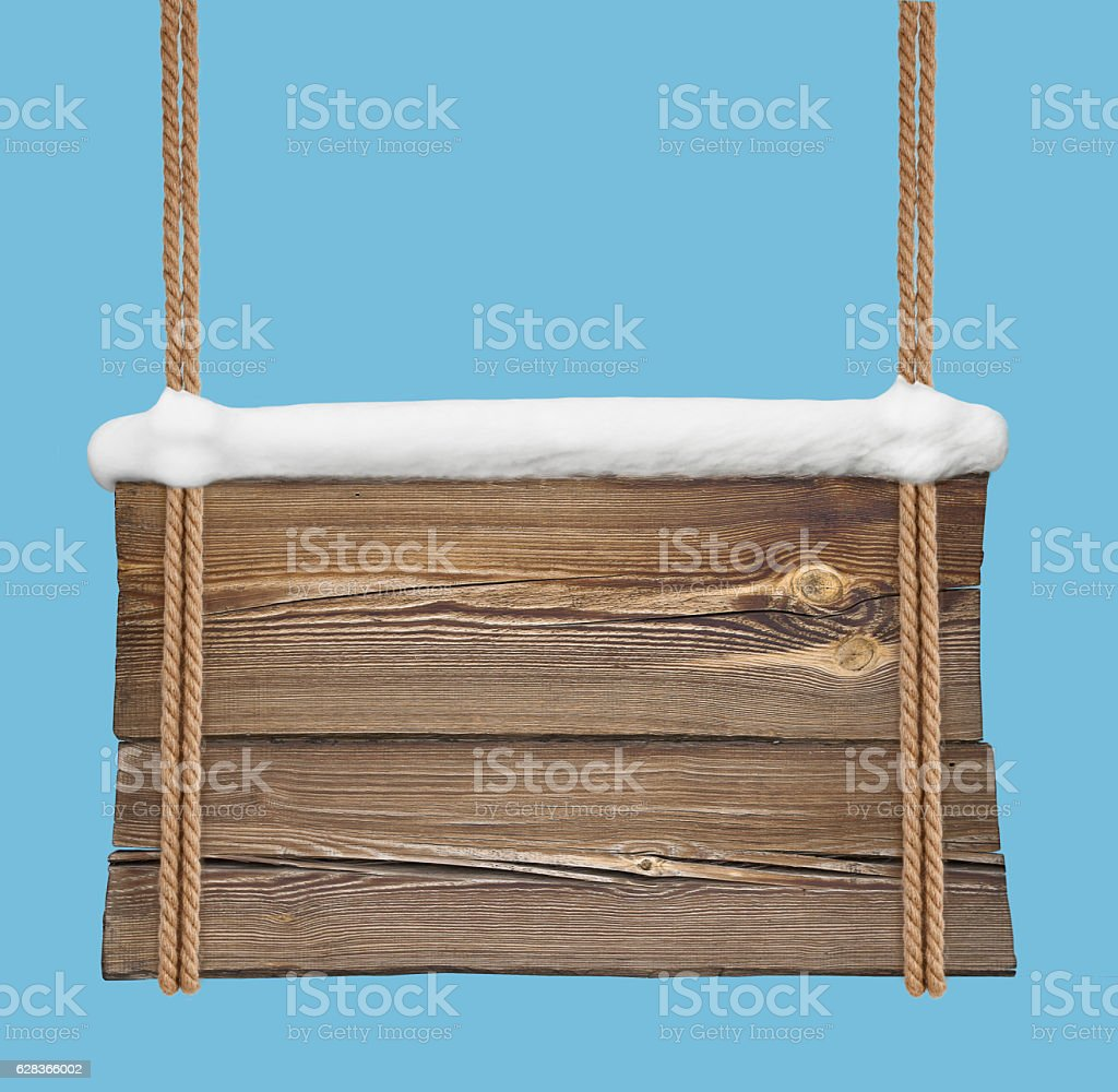 Wooden signboard with snow hanging on double ropes stock photo