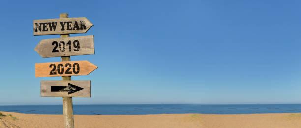 letrero sin vida feliz año nuevo en la playa con flechas opuestas 2020 y 2019 - foto de stock