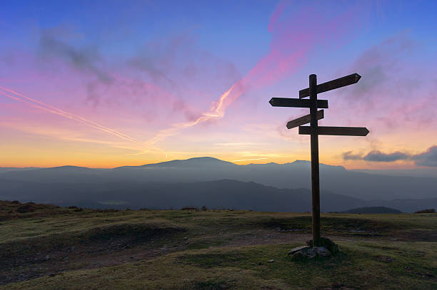 wooden signpost on mountain - directional sign stock photos and pictures