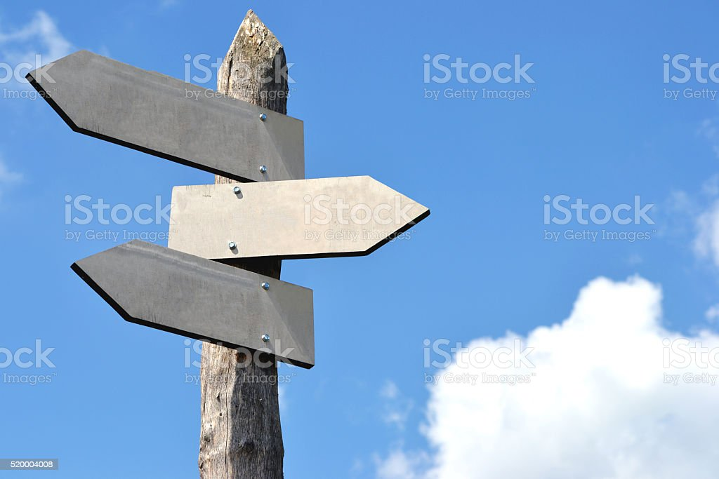 Wooden signpost with 3 arrows stock photo