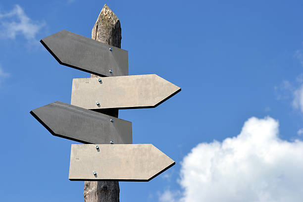 Wooden signpost with 4 arrows stock photo