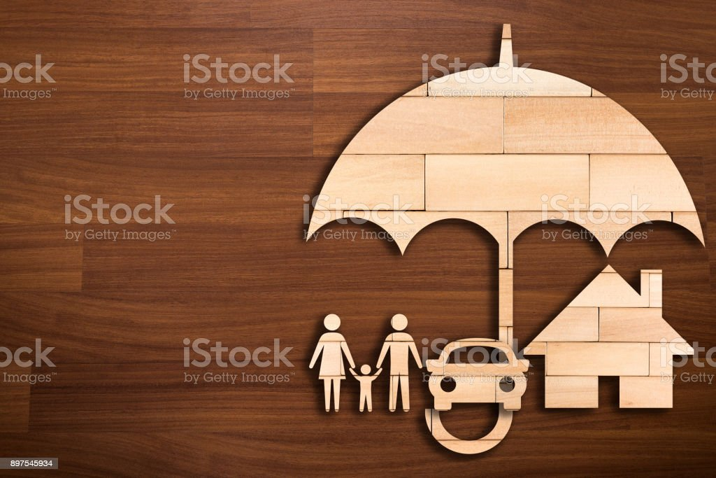 Wooden silhouette of family under umbrella - Concept of Insurance stock photo