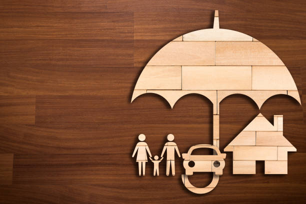 wooden silhouette of family under umbrella - concept of insurance - insurance stock photos and pictures
