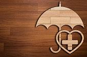 Wooden silhouette of medicine symbol under umbrella - Concept of Insurance