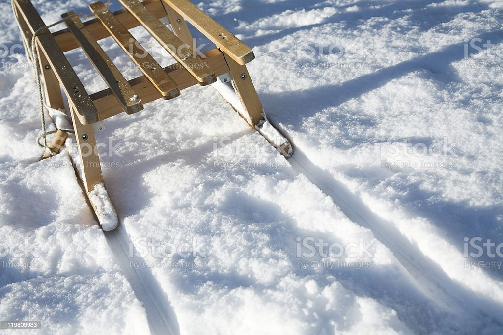 Wooden sled on white snow with tracks left behind in winter stock photo