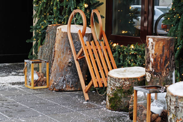 Wooden sled with stumps and glass candlesticks Wooden sled with stumps and glass candlesticks as christmas decoration near a cafe sleigh stock pictures, royalty-free photos & images