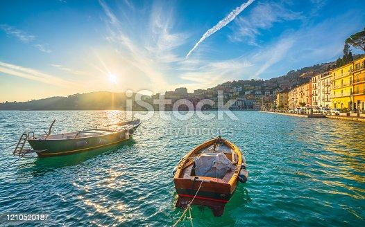 Wooden small boats in Porto Santo Stefano seafront at sunrise, italian travel destination. Monte Argentario, Tuscany, Italy.