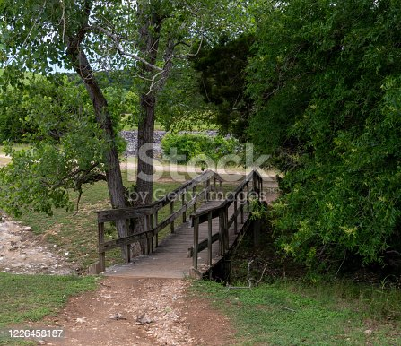 Wooden Small Bridge Crossing Small Water Stream With Large TRee on the Side