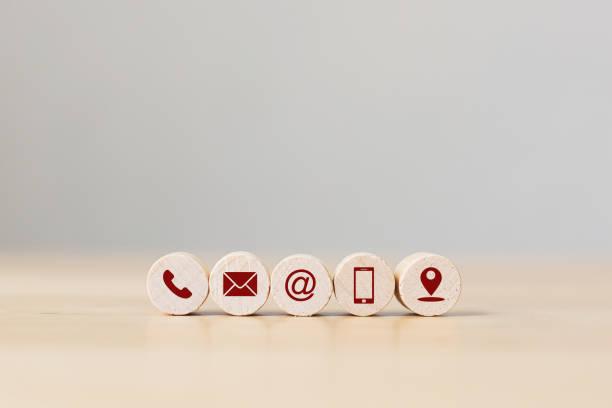 Esfera de madera con teléfono símbolo, correo electrónico, dirección móvil y ubicación. Conceptual de contacto con nosotros y concepto de marketing por correo electrónico - foto de stock