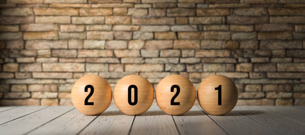 wooden spheres with number 2021 in front of a brick wall - 3D rendered illustration stock photo
