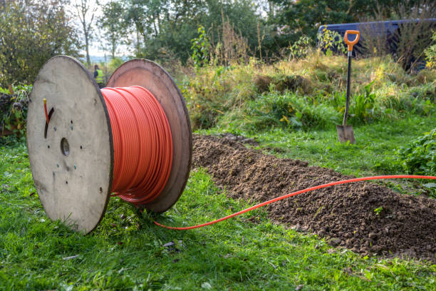 wooden spool with fiber optic cable for fast internet ready to be laid in narrow trenches in the ground on a meadow, infrastructure expansion in the countryside - włókno zdjęcia i obrazy z banku zdjęć