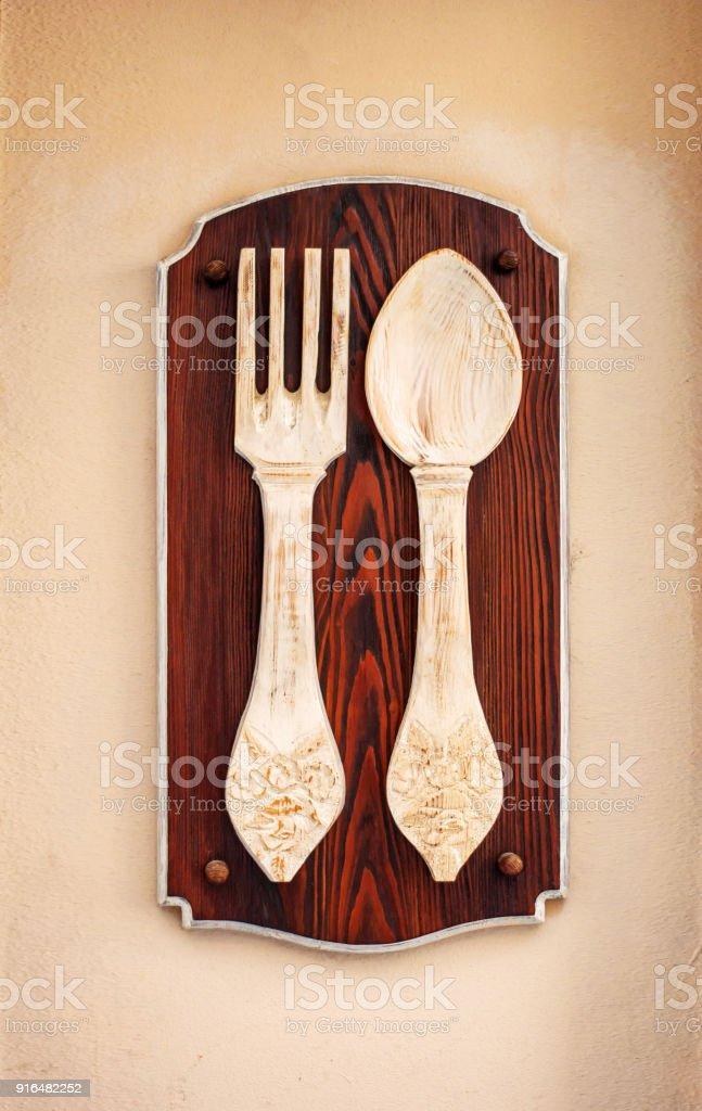 Wooden spoon and fork. Signboard for a vintage restaurant stock photo