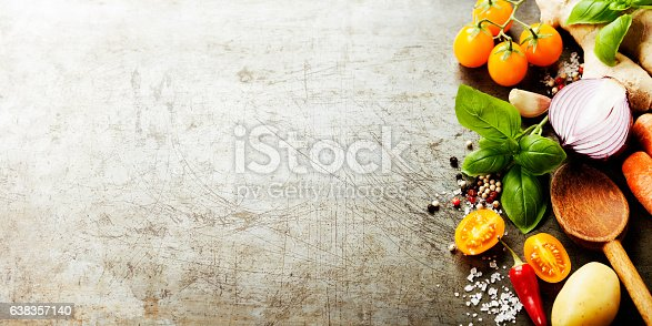 istock Wooden spoon and fresh organic vegetables on old background 638357140