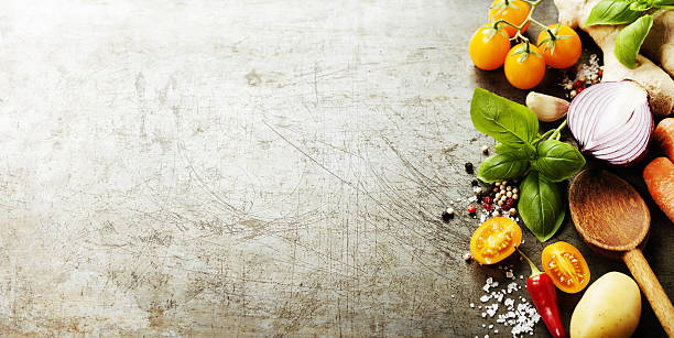 Wooden spoon and fresh organic vegetables on old background stock photo