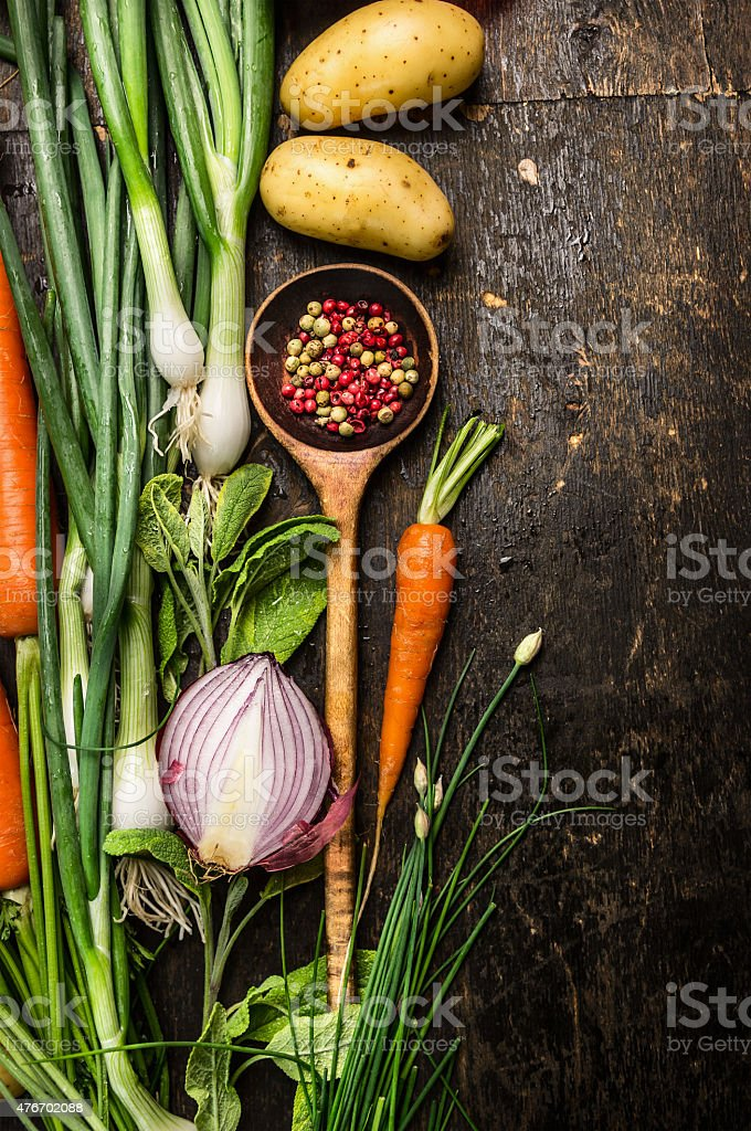 Wooden spoon and fresh vegetables ingredients on dark background stock photo