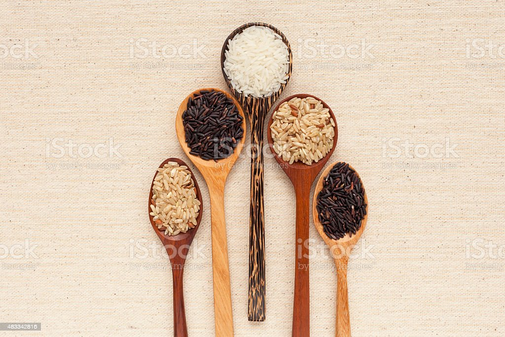 Wooden spoon and raw rice stock photo