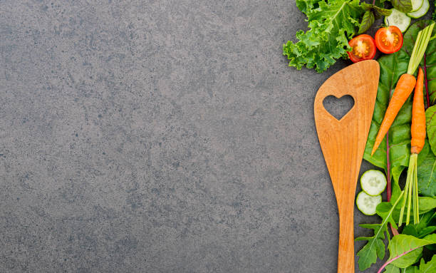 Holzlöffel und Gemüse auf dunklem Stein hintergrund. Gesundes Essen und Kochkonzept. – Foto