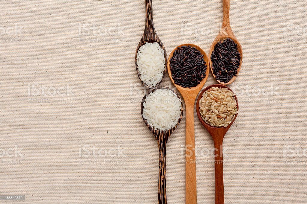 Wooden spoon collection and raw rice stock photo