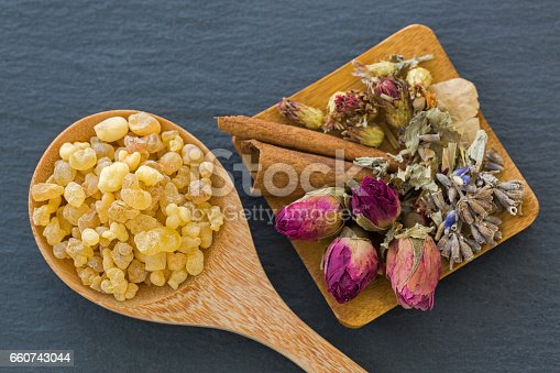 istock Wooden spoon of aromatic yellow resin gum next to dried flowers rose buds lavender cinnamon 660743044
