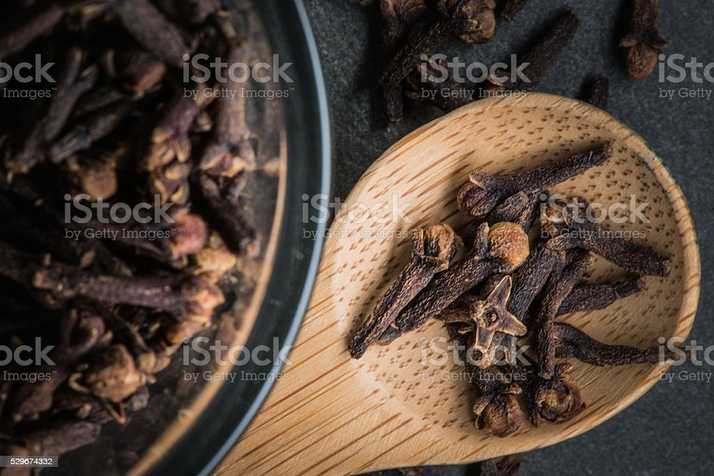 Wooden Spoon of Cloves sitting next to Glass Bowl stock photo