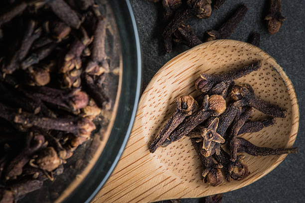 Wooden Spoon of Cloves sitting next to Glass Bowl Wooden Spoon of Cloves sitting next to Glass Bowl of Cloves on black cutting board clove spice stock pictures, royalty-free photos & images