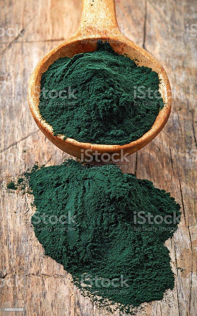 Wooden spoon of spirulina algae powder stock photo