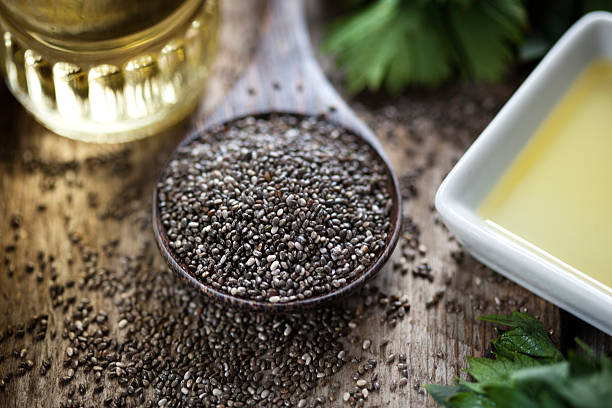 wooden spoon oil chia seeds - chia seed stock photos and pictures