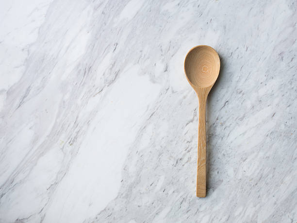 Wooden Spoon on white marble. Wooden spoon, fork, soup poon and plate on white venus marble. white marble stock pictures, royalty-free photos & images