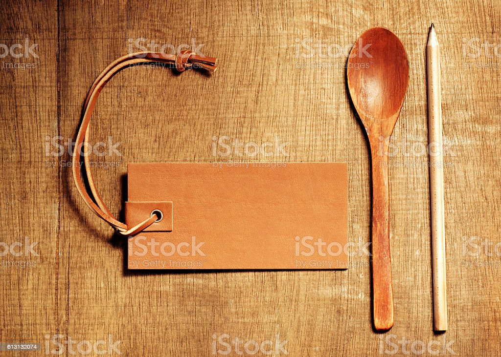 Wooden spoon on wood table background with leather blank for stock photo