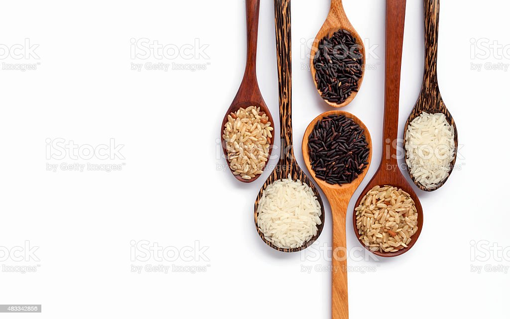 Wooden spoon set and rice on white background stock photo