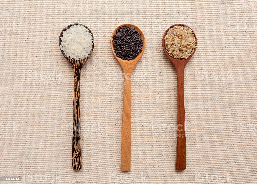 Wooden spoon set with rice on canvas stock photo