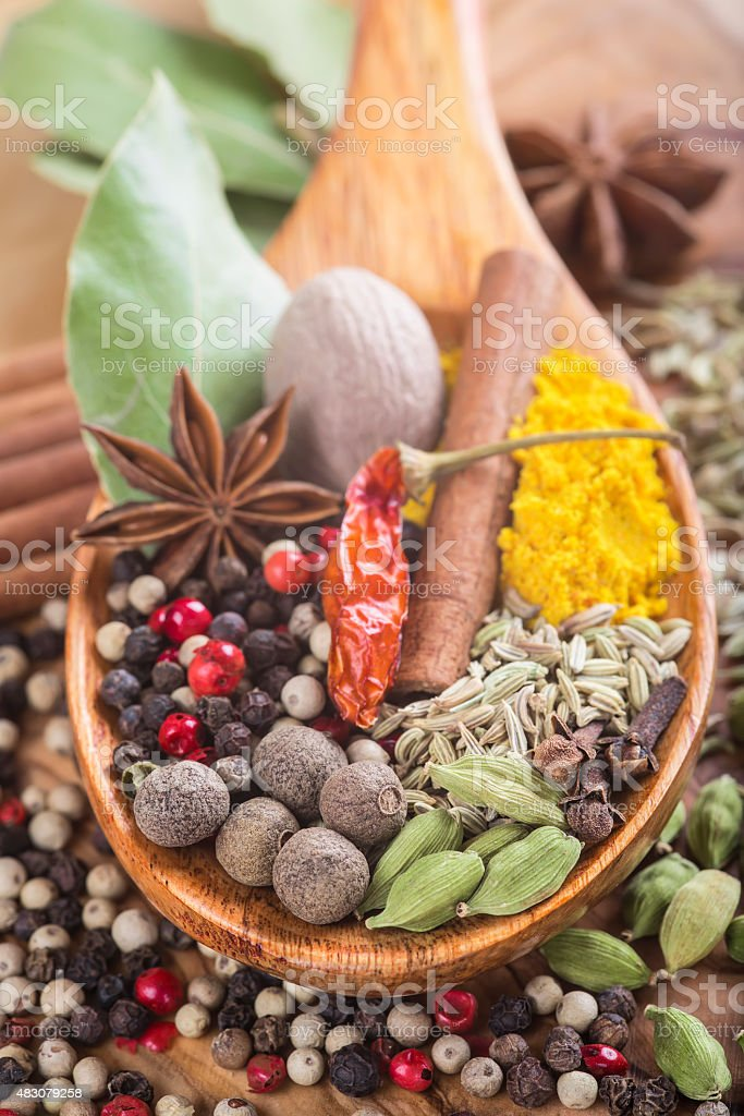 Wooden spoon with assortment of spices stock photo