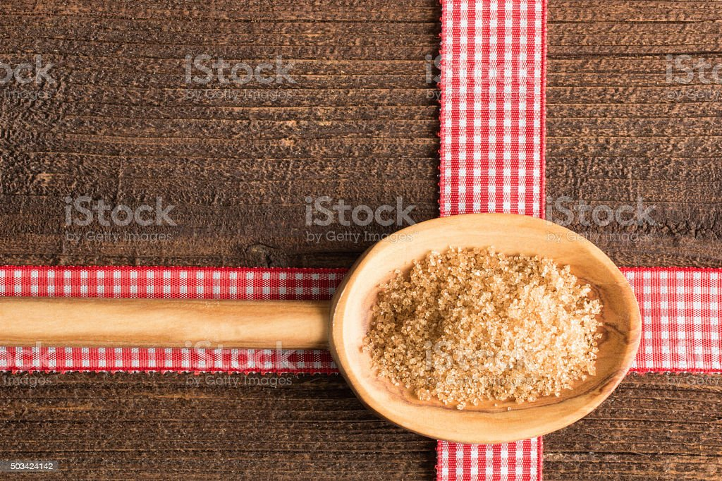 Wooden spoon with brown sugar stock photo