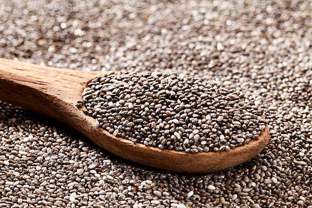 wooden spoon with chia seeds - chia seed stock photos and pictures