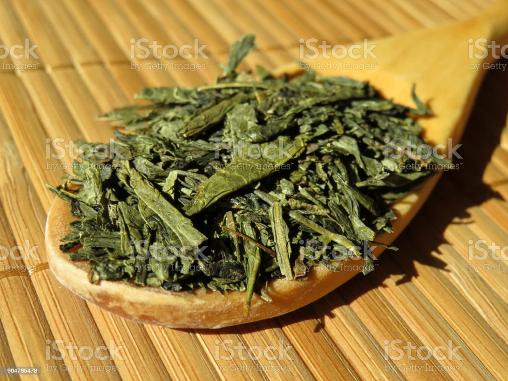 Wooden spoon with green tea dry leaves on bamboo table royalty-free stock photo