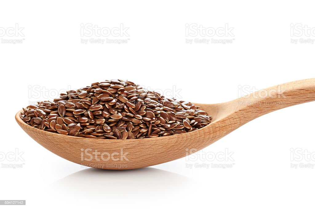 Wooden spoon with linen seeds isolated on white background. stock photo