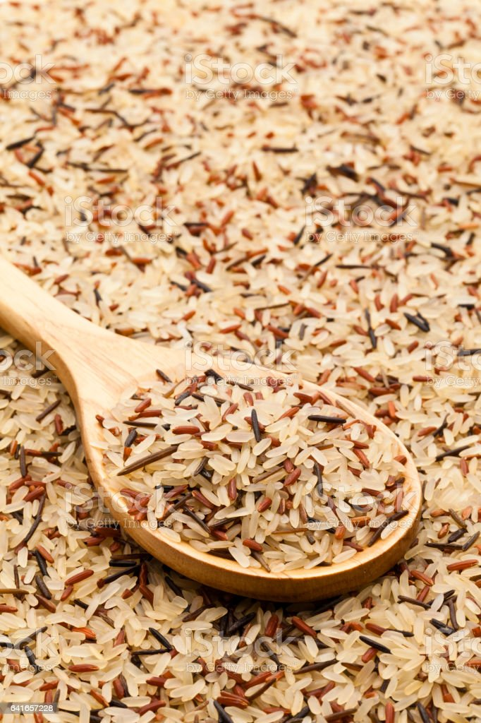 Wooden spoon with mixed rice grains on rice background stock photo