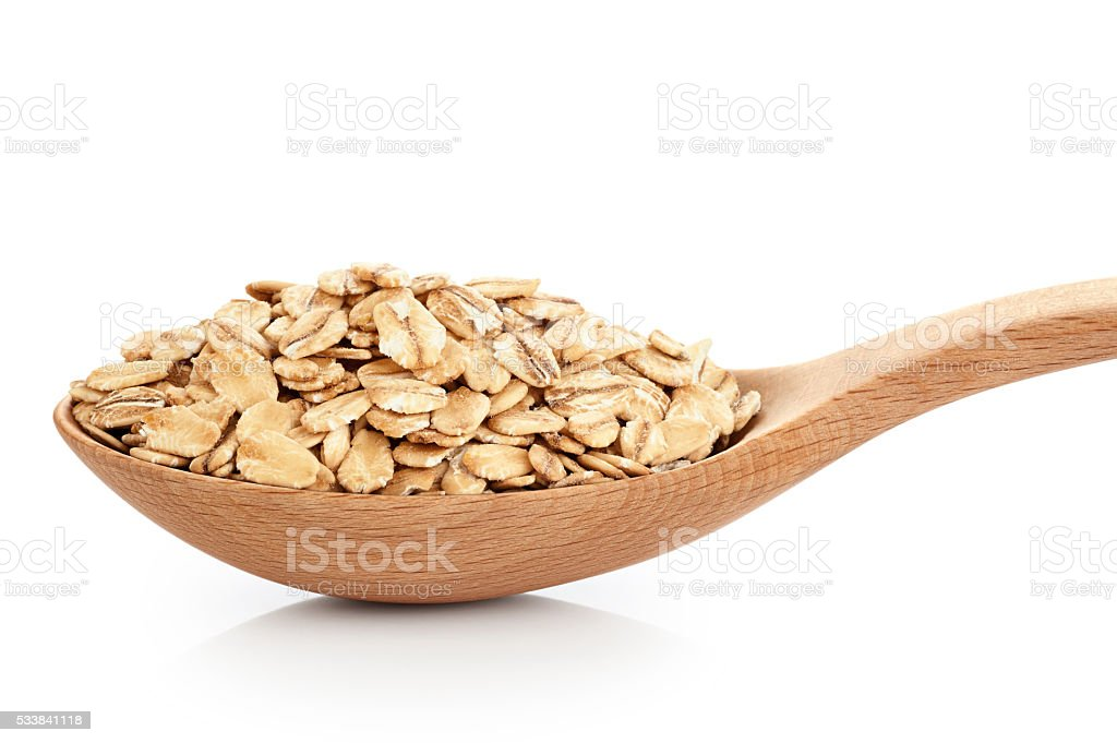 Wooden spoon with oats isolated on white background. stock photo