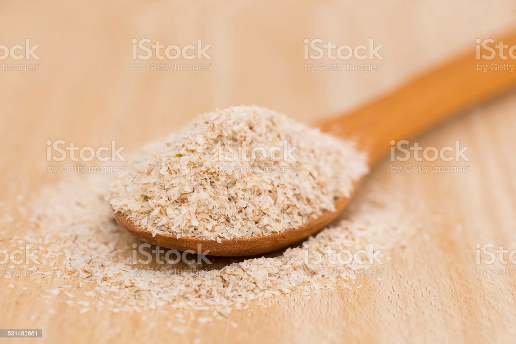 Wooden Spoon with Psyllium Seeds on wooden background stock photo