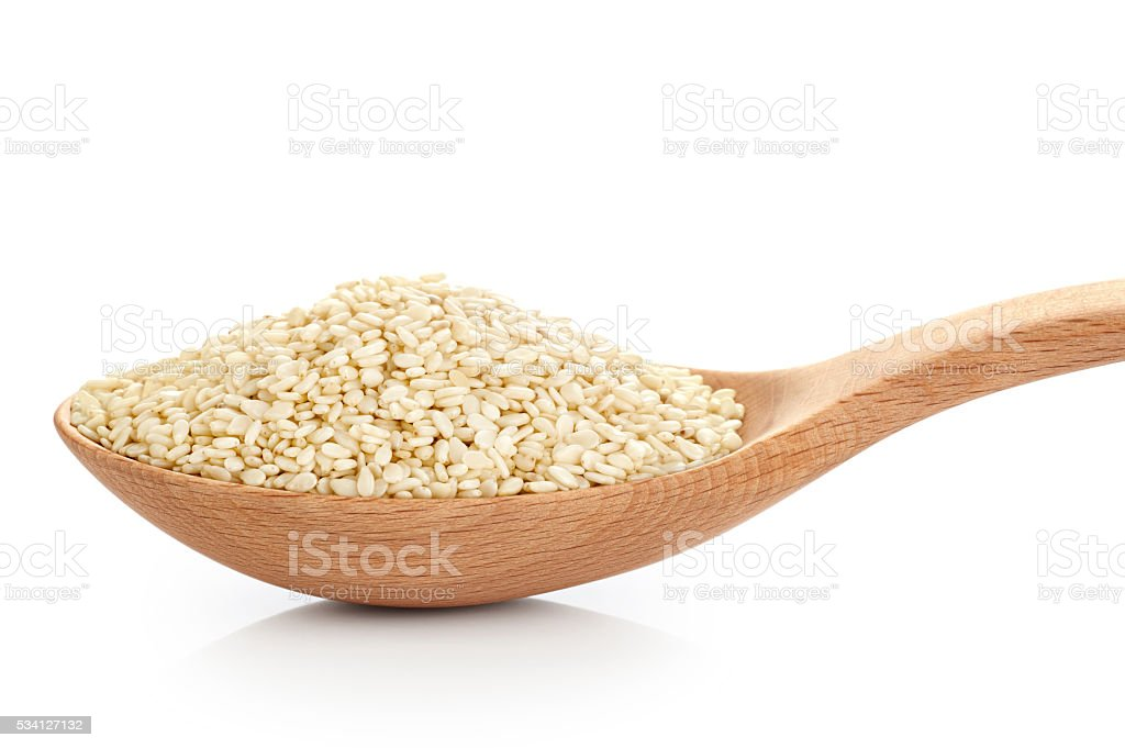Wooden spoon with sesame seeds isolated on white background. stock photo