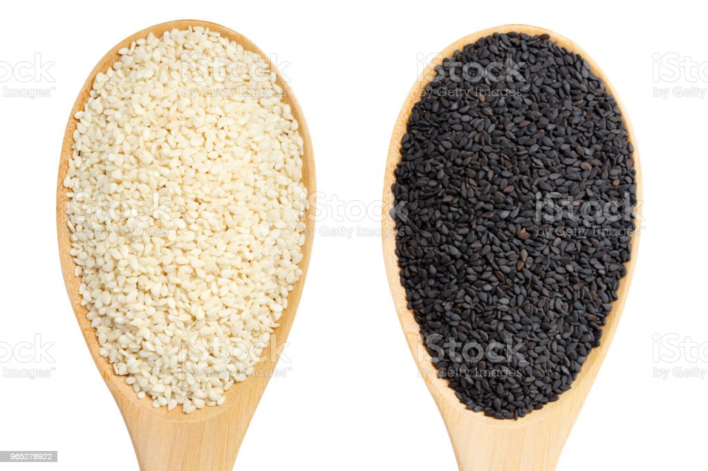 Wooden spoon with white and black sesame isolated on white background royalty-free stock photo