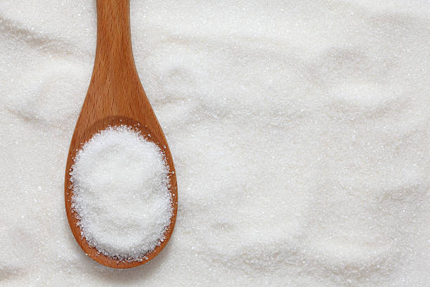 Wooden spoonful of white sugar just scooped up stock photo